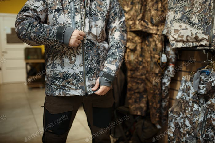 Man trying on uniform at showcase in gun shop
