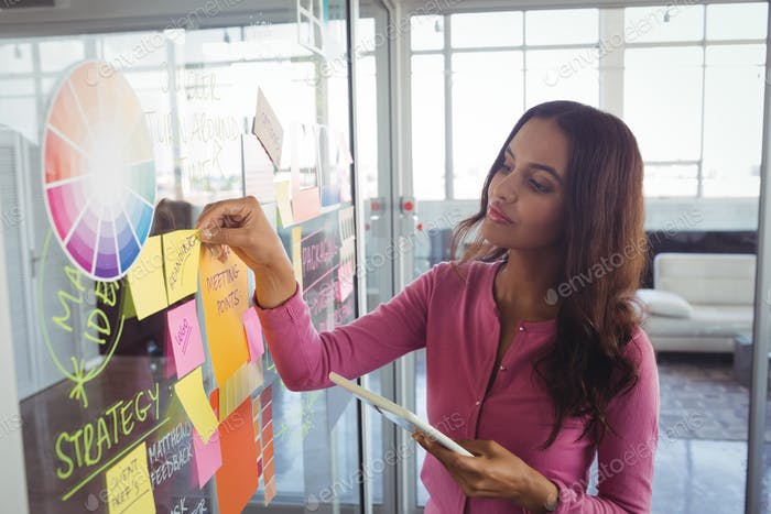 Female designer holding adhesive notes on glass in office