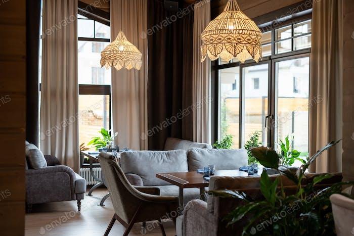 Part of luxurious restaurant with wooden tables and comfortable sofas