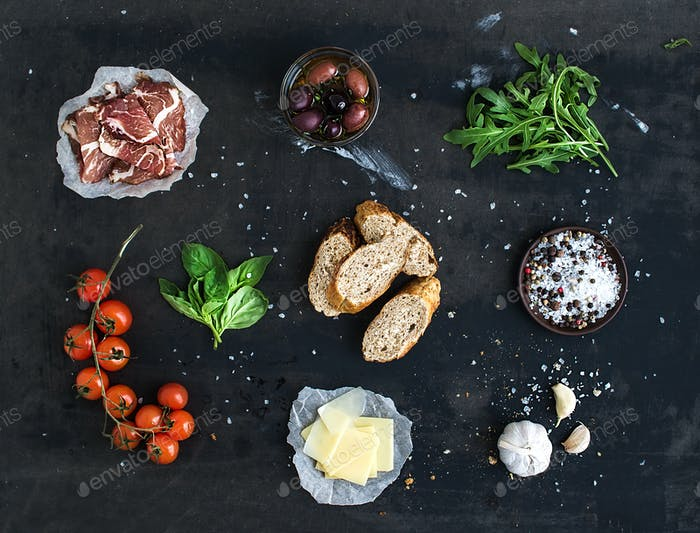 Ingredients for sandwich with smoked meat, baguette, basil, arugula, olives