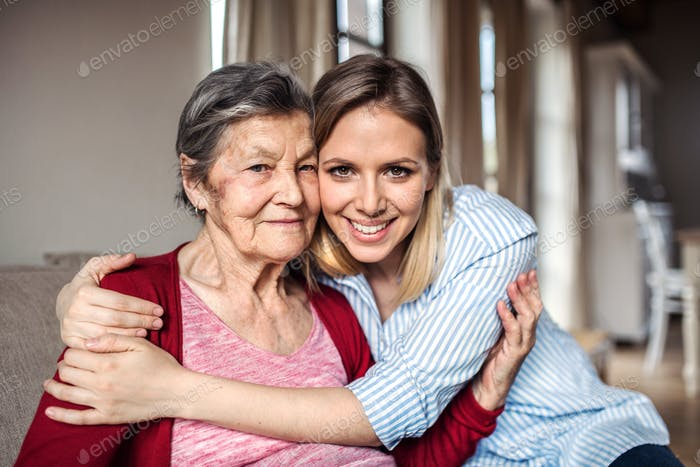 An elderly grandmother with an adult granddaughter at home, hugging.
