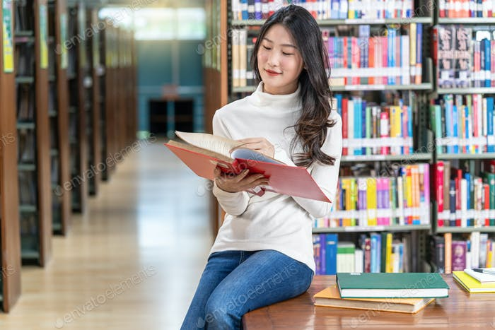 Asian young Student in casual suit reading the book in library of university or colleage