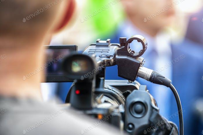 Pressekonferenz im Freien. Kameramann bei einer Medienveranstaltung