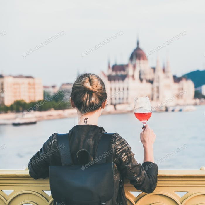 Woman standing with glass of wine in Budapest, square crop