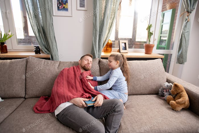 Careful cute little daughter putting warm woolen sweater on napping father