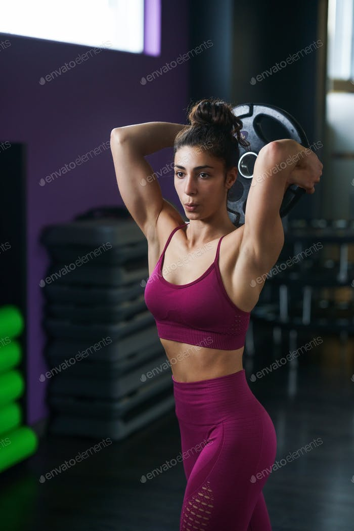 Athletic woman doing triceps push-ups with a barbell plate