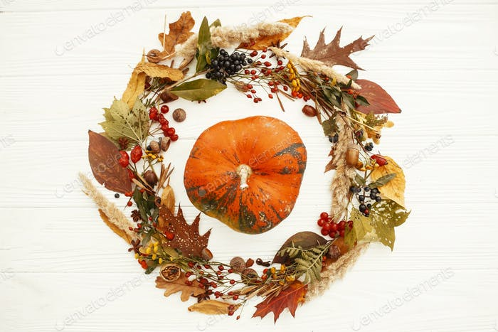 Pumpkin in beautiful fall leaves wreath with berries, nuts, acorns, herbs