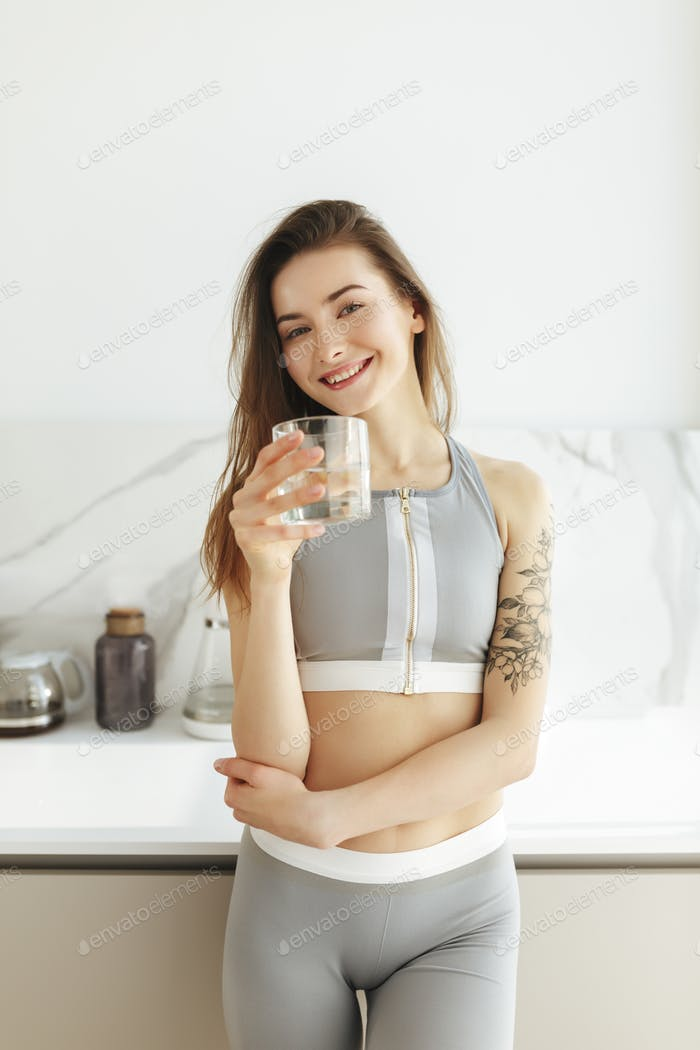 Beautiful lady in sporty top standing on kitchen and joyfully looking in camera with glass of water