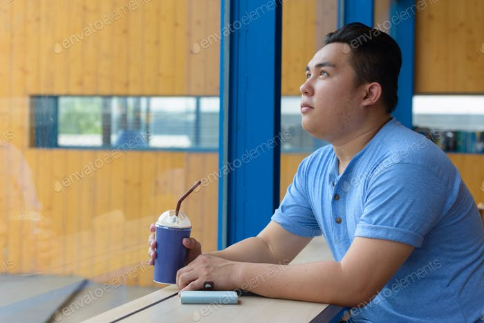 Young handsome overweight Asian man thinking at the coffee shop