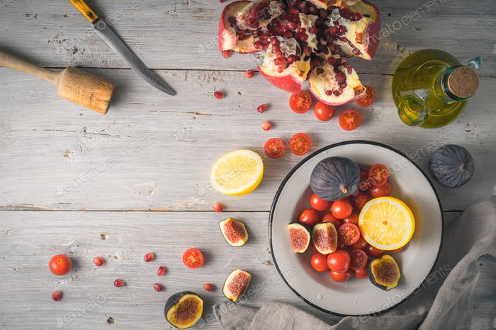 Pomegranate with figs and cherry tomatoes on the white wooden table top view