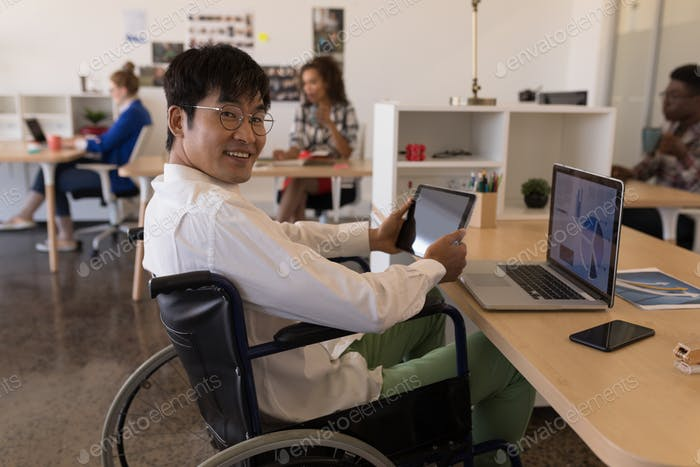 Side view of young disabled Asian male executive using digital tablet at desk in modern office