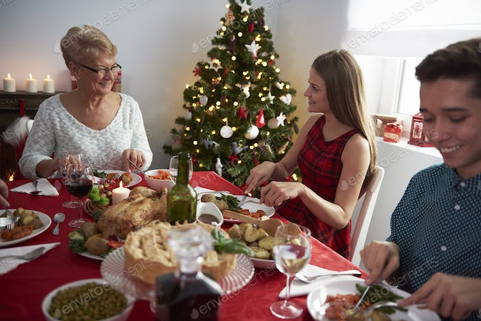 Grandmother and her grandchildren at Christmas table