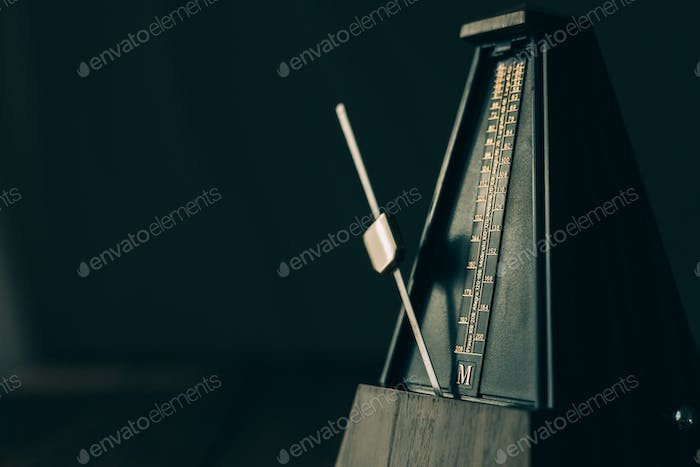 Vintage metronome, on a dark background.