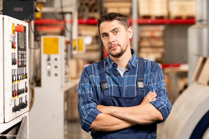 Young confident cross-armed factory worker or engineer by workplace