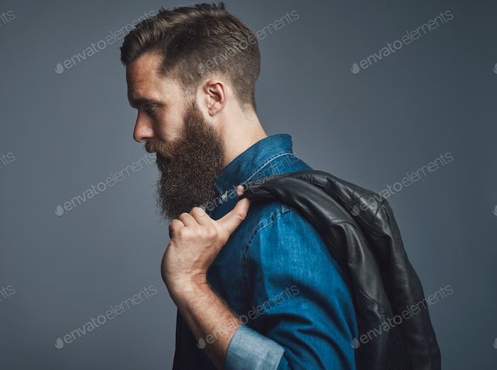 Side view on bearded man holding black jacket