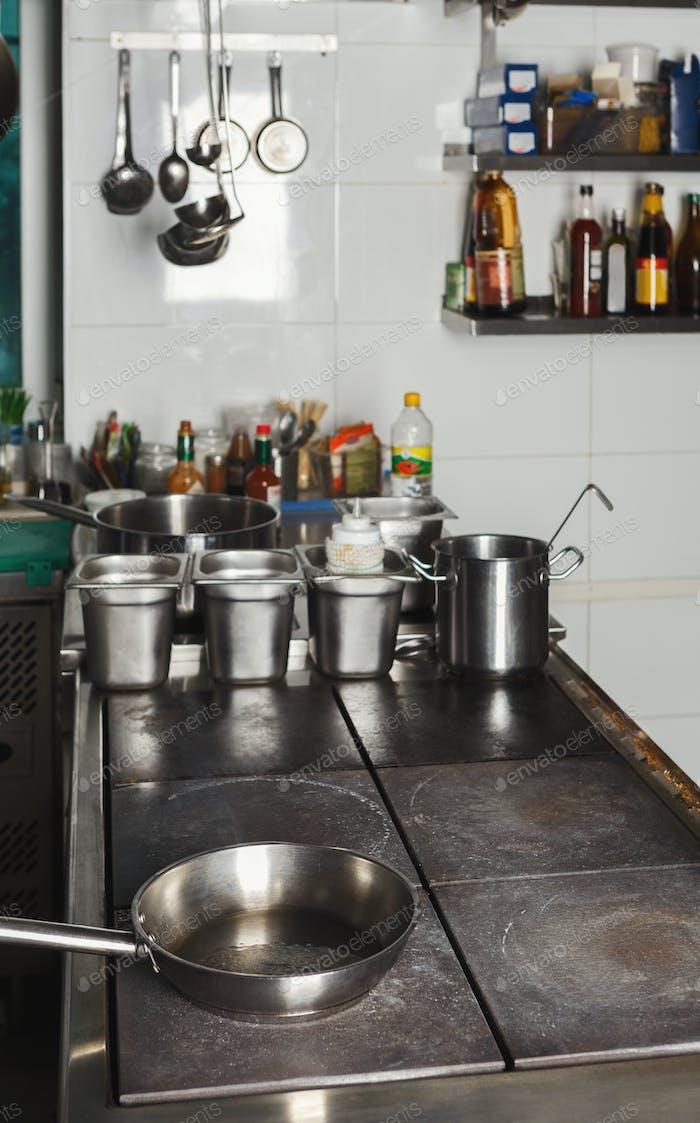 Modern restaurant kitchen interior with frying pans