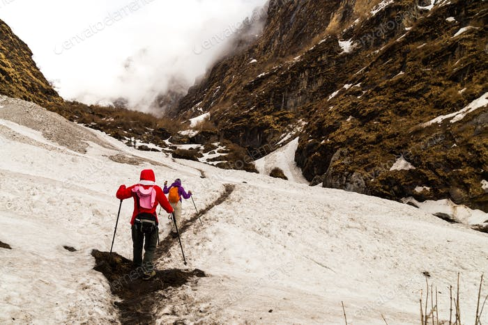 Two females hiking on a snowy trail towards the Annapurna mountains in Nepal