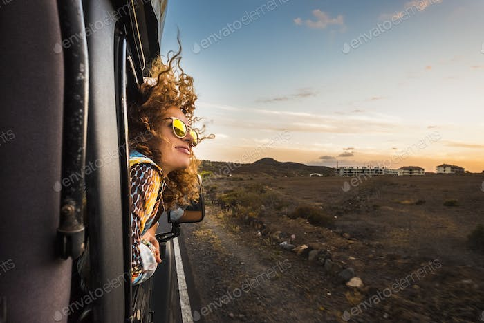 beautiful caucasian young woman travel outside the car with wind in the curly hair