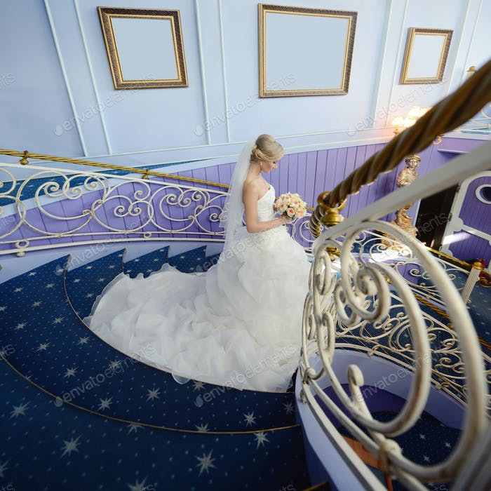 Novia de belleza en vestido de novia con ramo y velo de encaje en el interior