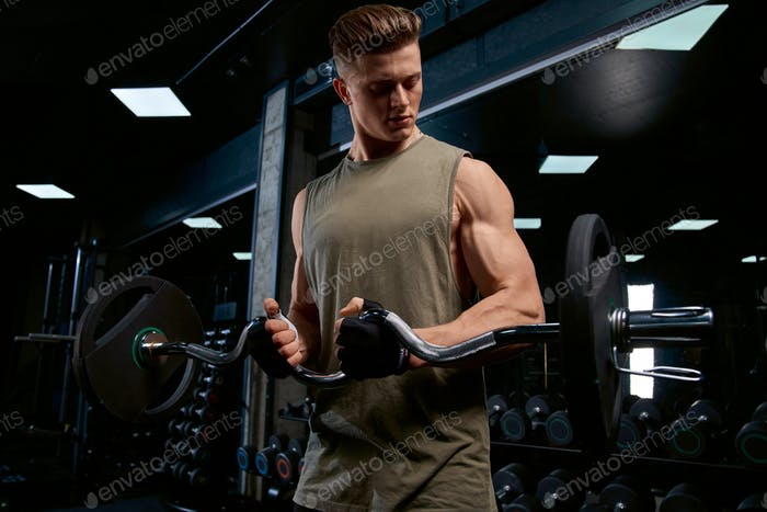 Muscular sportsman training biceps with barbell