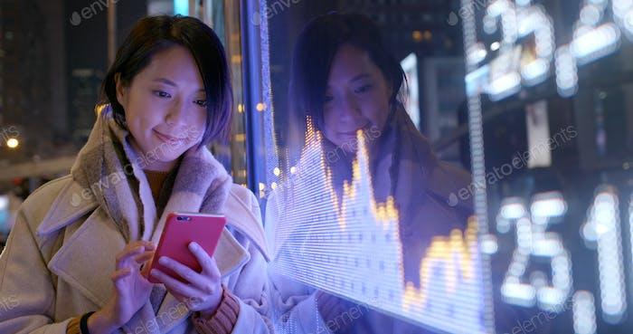 Frau Nutzung des Mobiltelefons, um die finanziellen Daten auf der Straße in der Nacht überprüfen