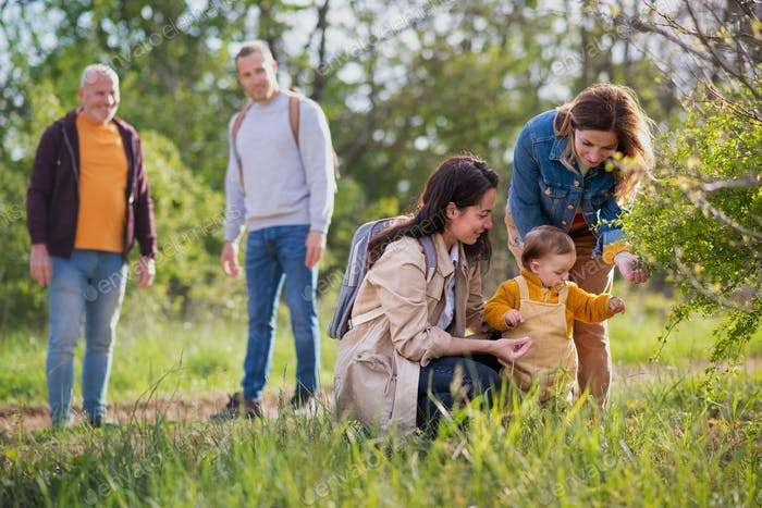 Small toddler with parents and grandparents on a walk outdoors in nature