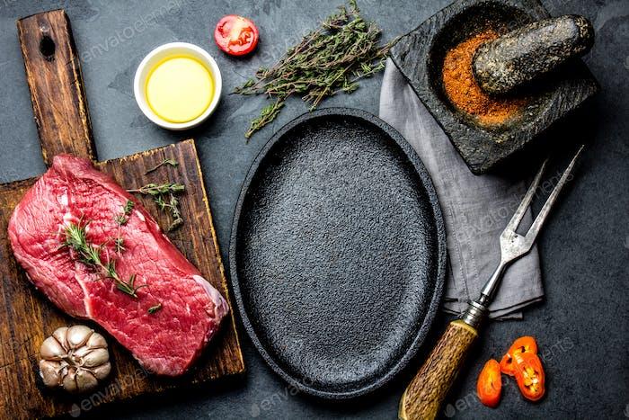 Rohes frisches Fleisch Steak Rinderfilet, Kräuter und Gewürze um Bratpfanne Teller.
