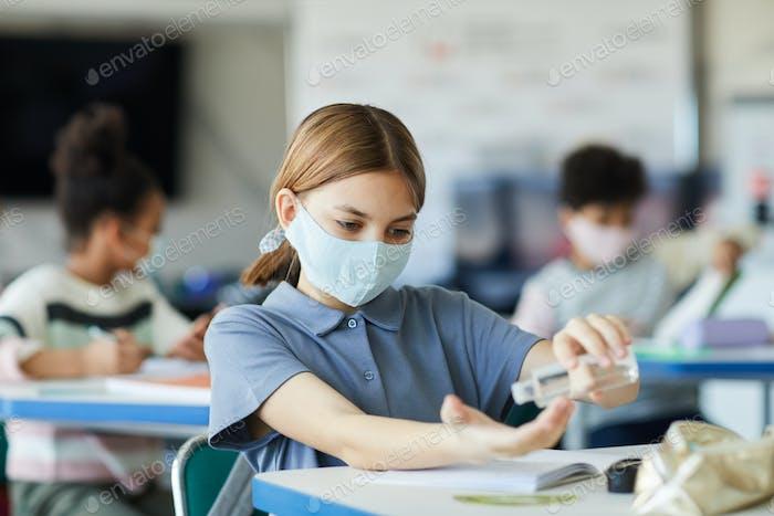 Cute Girl Sanitizing Hands in School
