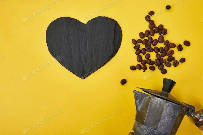 Flache Lage von Kaffeemaschine und Kaffeebohnen auf gelbem Hintergrund.