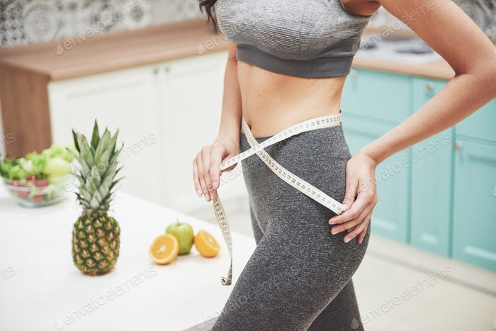 Portrait of a woman measuring her slim body on a kitchen background. Fitness and healthy lifestyle