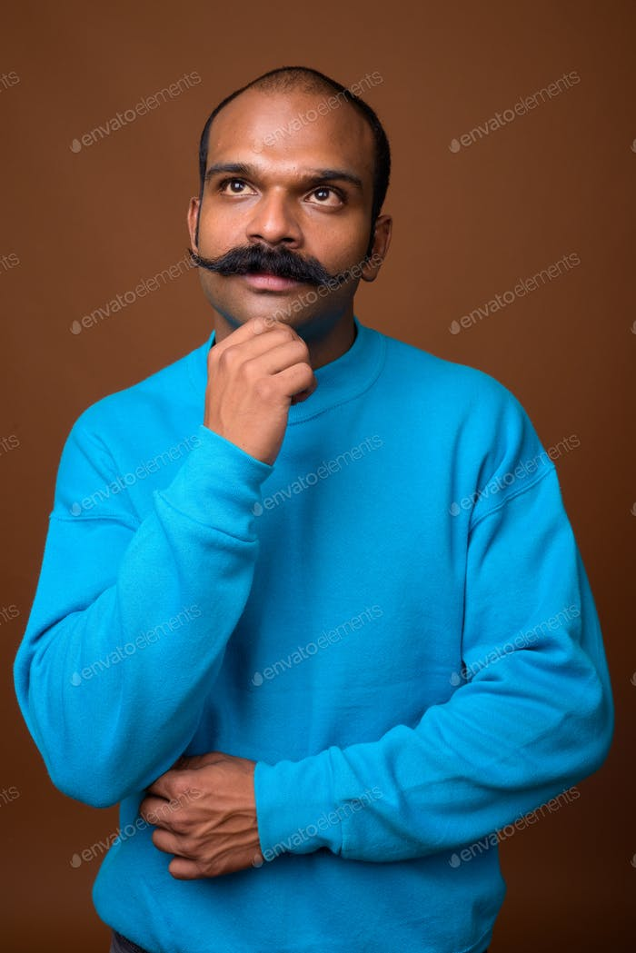 Portrait of Indian man with mustache wearing blue sweater