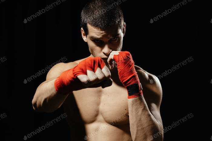 Athletic boxer punching with determination and precaution over black background