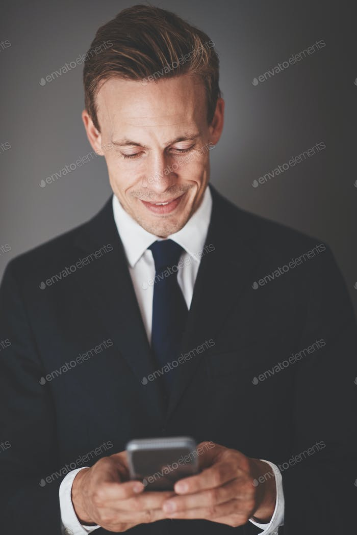 Young business executive sending text messages against a gray background