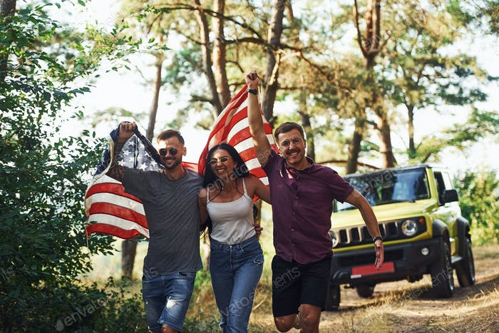 In the forest. Friends have nice weekend outdoors near theirs green car with USA flag