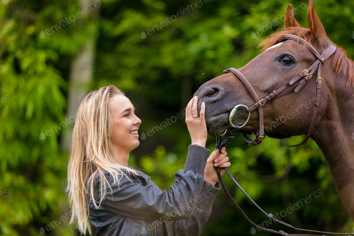 Close-up of smiling woman feeding her arabian horse with snacks