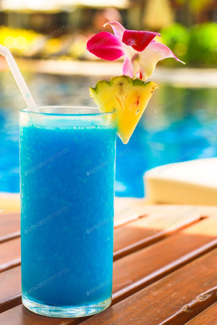 Tropical blue cocktail on a beach near swimming pool