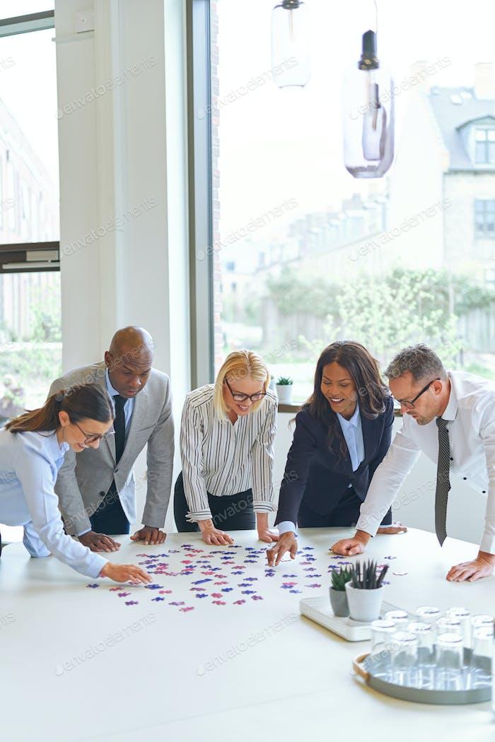 Lächelnde Geschäftsleute lösen ein Puzzle auf einem Bürotisch