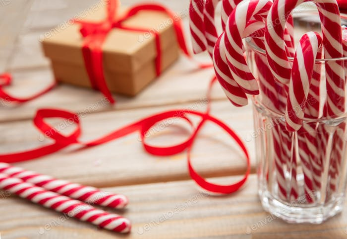 Candy canes in a glass, wooden background