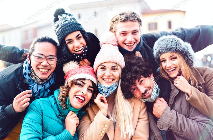 Multiracial friends taking selfie with open face mask and winter clothes