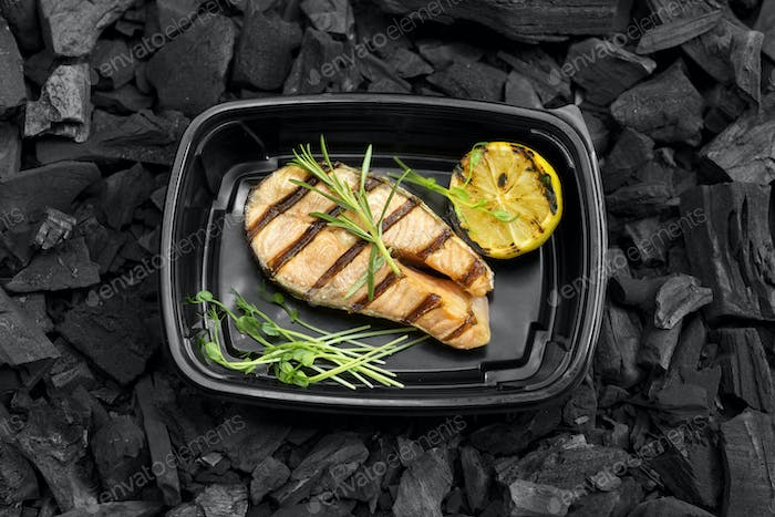 Tasty grilled fish with lemon and rosemary in to go box on coal