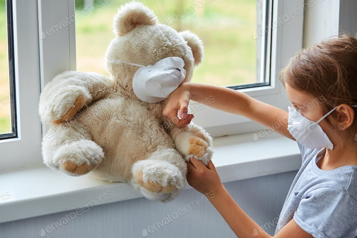Little girl holding and hugging teddy bear in mask.