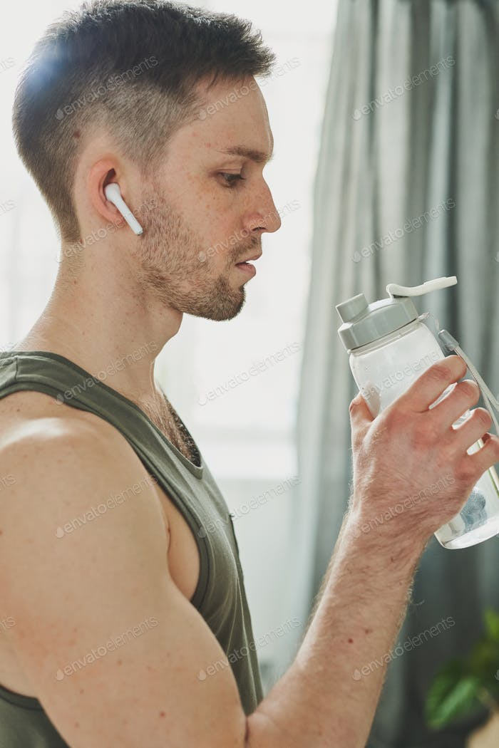 Young man in earphones and sports vest holding bottle of water by his mouth