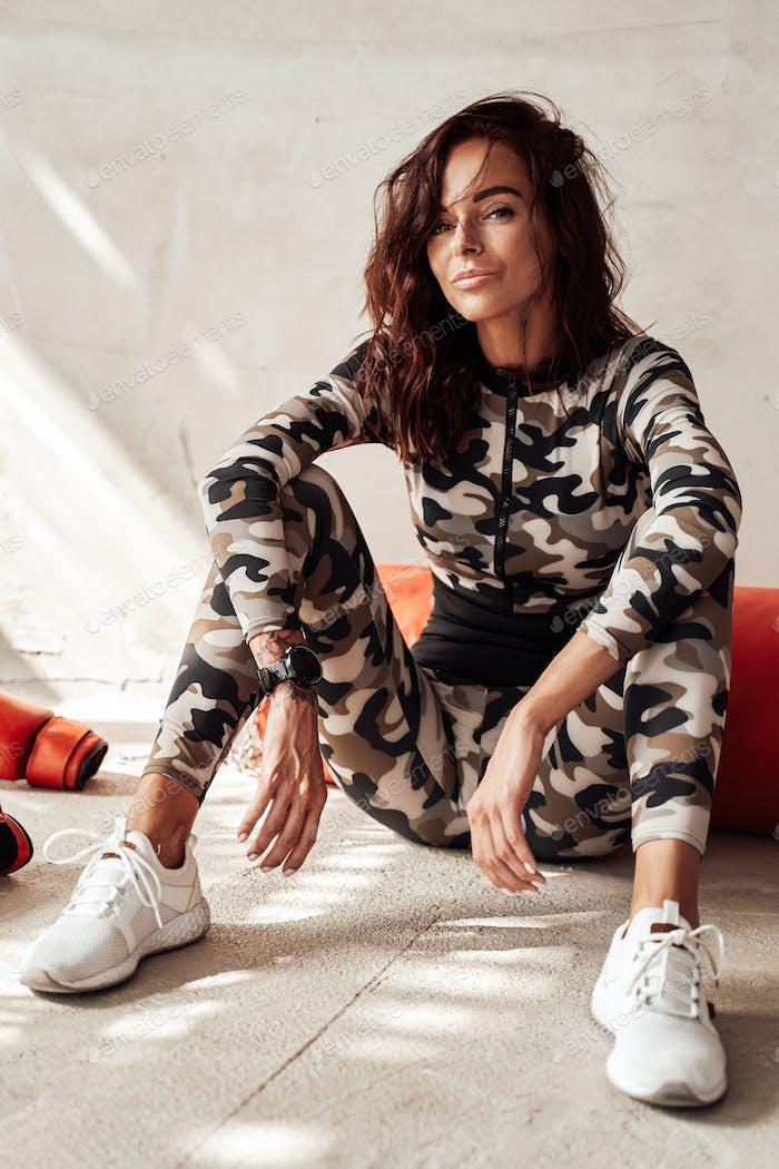 Frau in Camouflage Sportbekleidung ruht nach dem Training