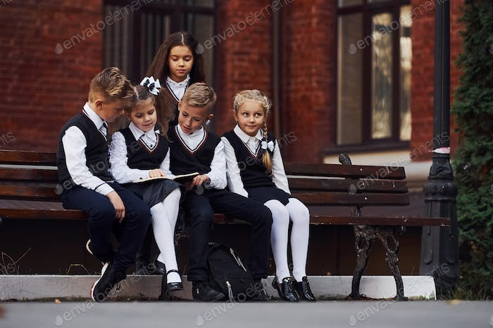 School kids in uniform that sits outdoors on the bench with notepad