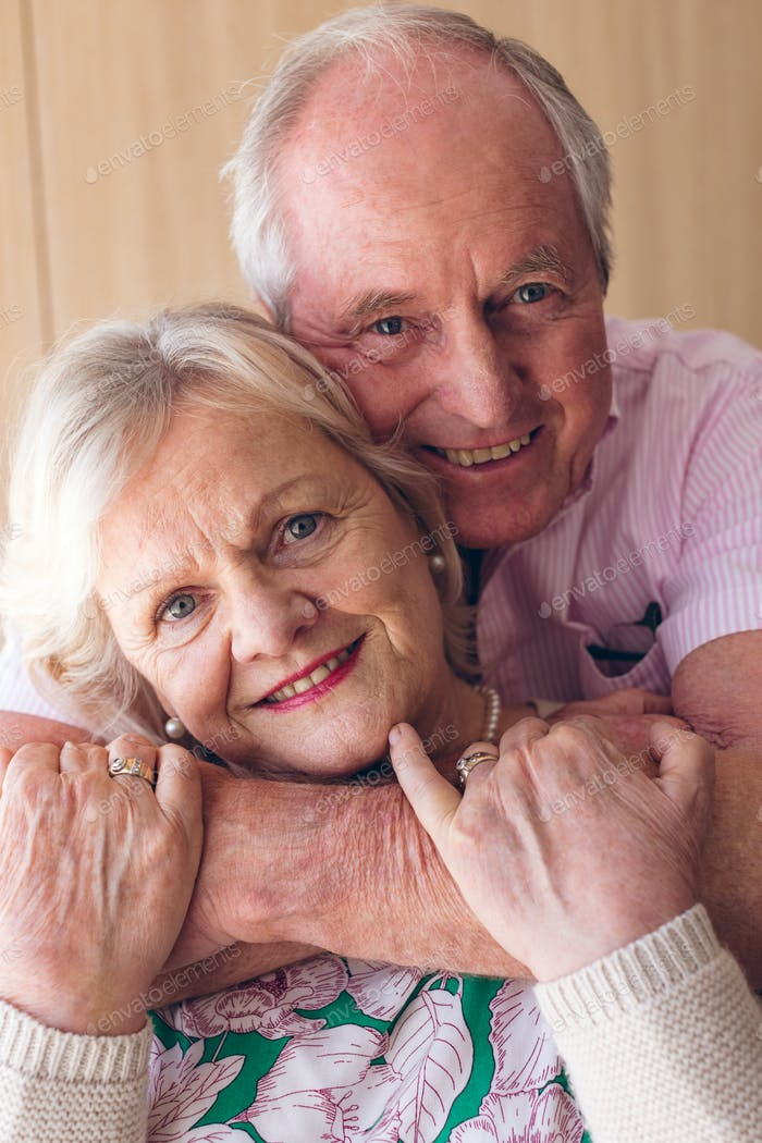 Close up of happy Caucasian senior couple posing while looking at camera at retirement home