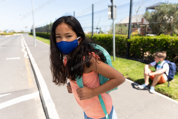Girl wearing face mask standing on the road
