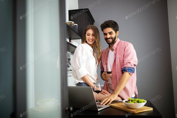 Happy couple using laptop while having breakfast in kitchen