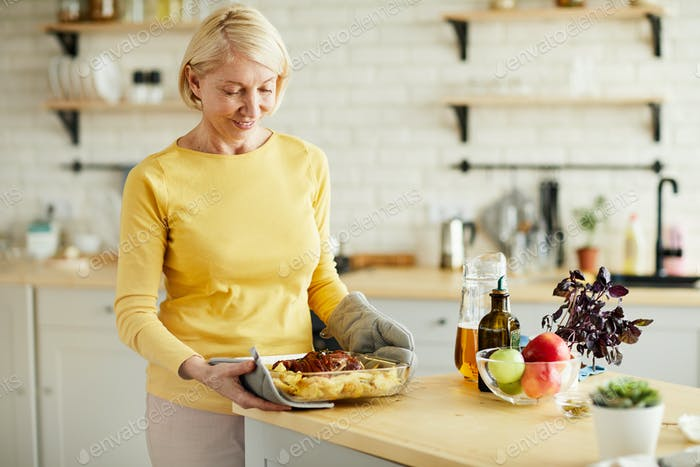 Mature woman taking hot dish out of oven