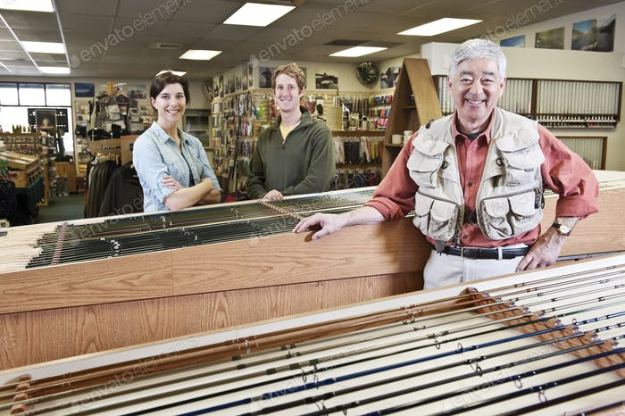 Asian American senior male owner of a retail fly fishing shop with two employees
