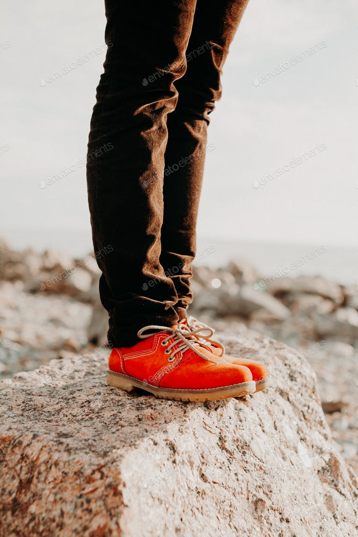 Woman in casual orange shoes and denim standing on stone in summer day. Fashion concept.